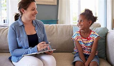 child therapist and young girl smiling