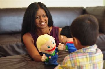 child therapist engaging a child with toy puppets