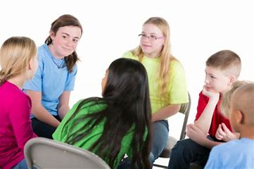 children sitting in a circle for group counseling