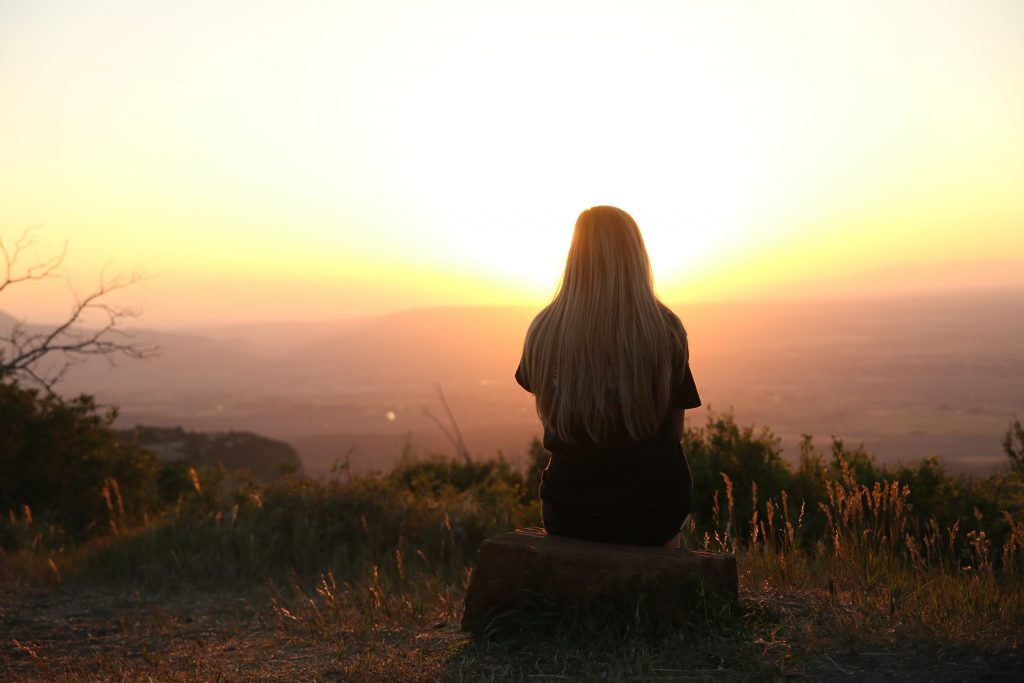 teen woman sitting on a hill looking at the sunset